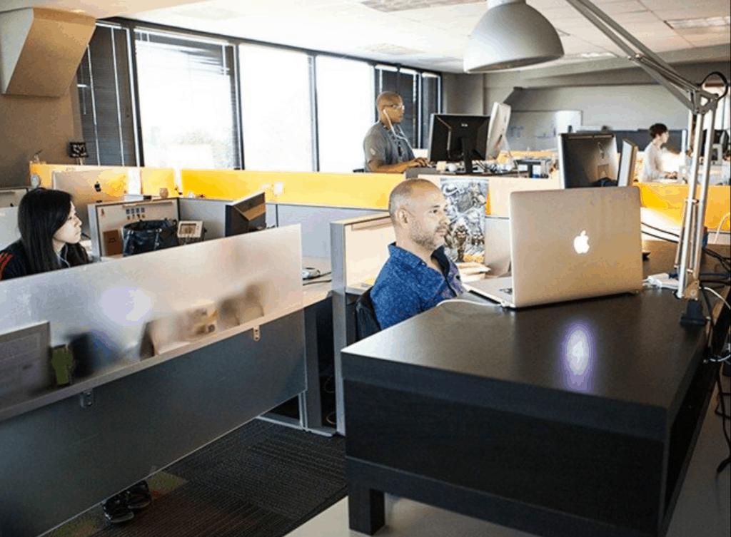 A photo pf the work environment at Kasasa, including corralled workstations and computer monitors