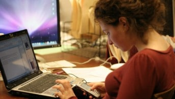A girl navigates her phone while using her laptop while studying at home